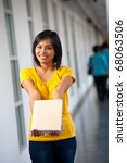 A beautiful college student in yellow standing in hallway showing cover of a blank book where text can be inserted on university campus.  Female Asian Thai model of Chinese descent looking at camera - stock photo