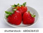 three red ripe strawberries in... | Shutterstock . vector #680636410