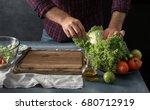 man cooking vegetables salad in ... | Shutterstock . vector #680712919