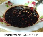 Small photo of Hot chilied soy sauce in a small white bowl. Delicious addon to add spiciness in the food. Visible flower pattern on the bowl
