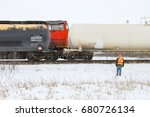 A crew member watches a passing train looking for issues - stock photo