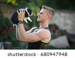 Stock photo muscle young man holding cute border collie puppy 680947948