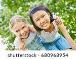 two happy girls as friends hug... | Shutterstock . vector #680968954