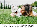 Stock photo beautiful young woman playing with her little west highland white terrier in a park outdoors 680989840
