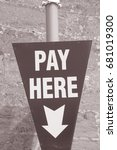 Small photo of Pay Here Sign against Stone Wall in Black and White Sepia Tone