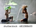 Two Boys Playing In A River In...
