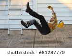 Small photo of Worker with hard hat falling from ladder onto concrete floor