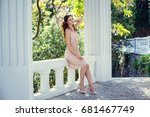 Stock photo fashion outdoor photo of gorgeous woman with dark hair in elegant pink dress posing at summer park 681467749