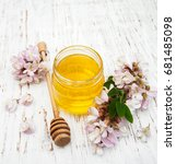 Small photo of honey with acacia blossoms on a wooden background
