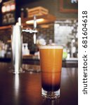 Small photo of frothy sparkling nitro cold brew ready to be served at coffee shop bar environment background. coffee machine wooden table vivid colorful vintage