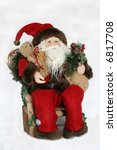 santa sitting in chair holding toys - stock photo
