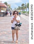 Small photo of Hollywood, Florida - July 13, 2017: Many visitors who enjoy the boardwalk, beach and ocean but still are unable to put down their cell phones.