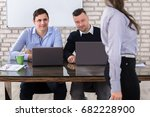 Small photo of Close-up Of Businessmen Using Laptop Looking At Woman In Office