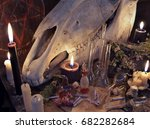 Small photo of Witch table with black candle, horse skull, magic bottles and paper scrolls. Mystic still life with scary occult objects, horror Halloween and black magick concept, alchemic or witch laboratory