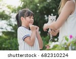 Stock photo asian mother giving a kitten to her daughter 682310224