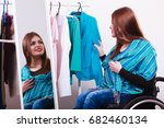 Small photo of Real people, disability and handicap concept. Teen girl handicapped woman sitting on wheelchair choosing clothes in wardrobe or looking for some clothes in shop