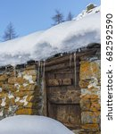 Small photo of Soana Valley, Piedmont, Italy - December 2016: Wooden door and snow covered roof of alpine stone hut.