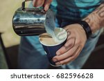 a barista pours steamed milk in ... | Shutterstock . vector #682596628