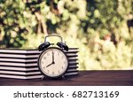 a stack of books and an alarm... | Shutterstock . vector #682713169