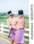 Small photo of Muadzam Shah, Malaysia - July 21st, 2017 : Young stylish handsome twins are preparing to wear a Malay traditional Malay clothing at First Dairy Farm , Malaysia. Happiness Concept.