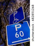 Small photo of P (wheelchair symbol) above P 60 (Parking 60 minutes) sign. Blue and white. Tree branches and sky in background