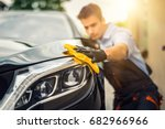 Stock photo car detailing the man holds the microfiber in hand and polishes the car selective focus 682966966