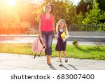 Small photo of Mom and schoolgirl of primary school holding hands. The parent takes the child to school. Outdoors, return to the concept of the school
