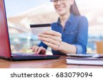 Small photo of Online shopping. Beautiful smiling young woman sits in front of a laptop and holds a bank card and enters a card number for the order of goods