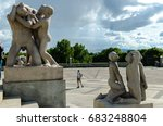 """Small photo of FROGNER PARK, OSLO, NORWAY - AUGUST 23, 2014: Gustav Vigeland's granite sculpture of """"Two boys teasing an imbecile man"""" completed in 1923 (left) and boys gazing at the sky"""