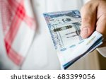 saudi man holding or paying... | Shutterstock . vector #683399056