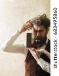 Small photo of Hipster with bottle of wine and glass standing on female hands. Bearded man with long beard, moustache and messy hair on beige wall. Alcohol abuse and alcoholism. Unhealthy lifestyle. Bad habits