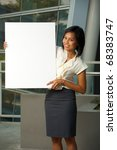 Attractive, smiling Asian business woman in white blouse holds a blank sign outside in front of a modern office complex.  Custom text copy space insert. Female Asian dark skin model Chinese descent - stock photo