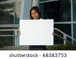 A cheerful and cute corporate professional holds an empty placard in front of an office building.  Custom text insert.  20s female Asian Thai model of Chinese descent. - stock photo