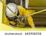Small photo of Working at height. A commercial abseiler hanging on main structure of oil and gas platform. Focusing on abseiling equipment.