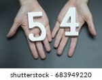 Small photo of On a black background, female hand with number fifty-four.