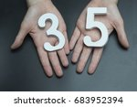 Small photo of On a black background, female hand with a figure thirty-five.