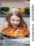 Small photo of A girl with flour on her face staring at a pie with amazement.