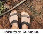 Small photo of Dirty sandals and foot in garden