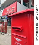 Small photo of July 21, 2017: Red pillar box in front of Khukhot Post Office, Pathumthani,Thailand. it is a large red Square shape public mailbox.