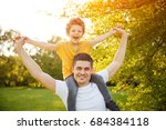 young smiling father carrying... | Shutterstock . vector #684384118