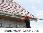 worker installs the gutter... | Shutterstock . vector #684812218