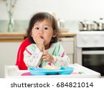 baby girl eating  pasta at home | Shutterstock . vector #684821014