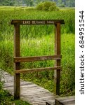 Small photo of Sign to a hiking trail leading into tall grass prairie fields.