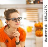 Small photo of Frightful Treats all the way. Portrait of young woman in party bat glasses in the Halloween decorated kitchen looking aside