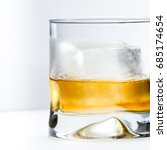Small photo of blended scotch whiskey served in a short glass with a large ice cube isolated on a white background
