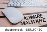 Small photo of Conceptual image of Adware and Malware words for online awareness with mouse and keyboard over nice wooden background