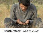 a man praying in a field | Shutterstock . vector #685219069