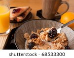 Close up of a spoon full of breakfast cereal flakes with almonds and blackberries.  Shallow depth of field. - stock photo