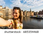 Stock photo view of a tourist girl on sunset at the damrak square in amsterdam 685354468