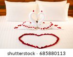 Stock photo fold a towel couple swan for decorations with rose petals on wedding bed 685880113
